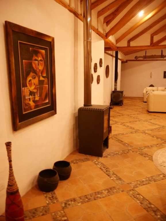 Hôtel Hacienda Los Mortiños, Parc Cotopaxi, Equateur, salon avec cheminée et peinture de Guayasamin